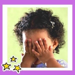 A small girl with curly hair hides her face behind her hands.