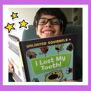 A boy smiles over the top of a book. The book he is reading is I Lost My Tooth.