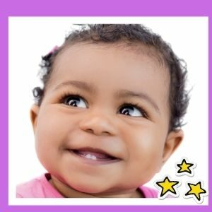 An infant girl gives a big smile, showing her two bottom teeth.