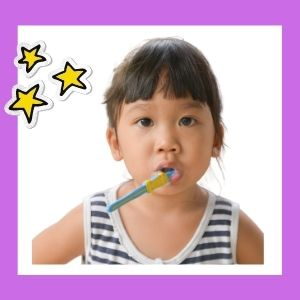 A girl looks at the camera with a toothbrush in her mouth and a hand on her hip.