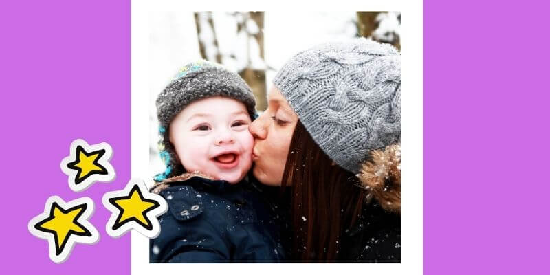A woman holds a toddler while kissing his cheek.