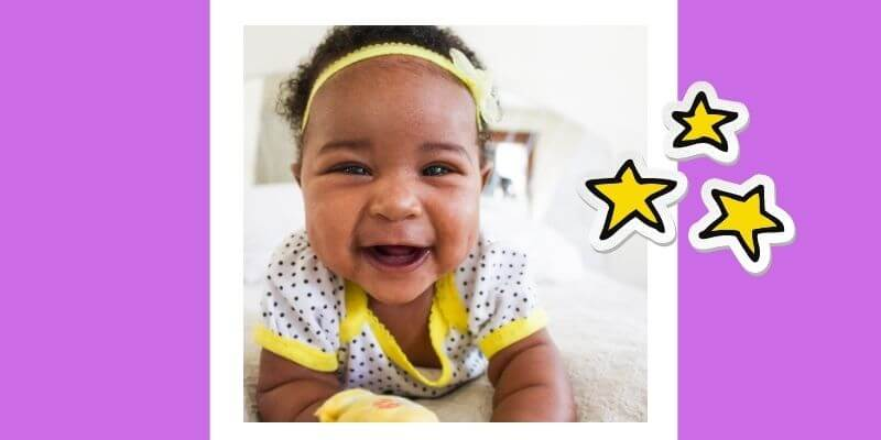 A baby girl crawls toward the camera with a big toothless smile.