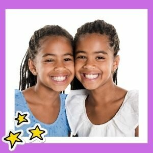 Twin girls who are young teenagers smile at the camera.