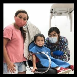 Dental assistant, Liz, poses with a family by the X-Ray machine.