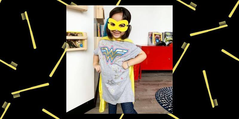 A young girl wears a mask and cape in the Super Kids Austin office.