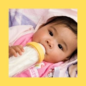 A baby holds on to her bottle while drinking and looking at the camera.