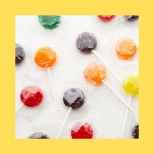 Plastic wrapped lollipops scattered on a white background.