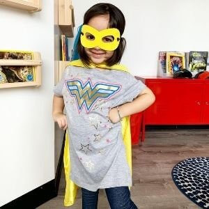 A young girl wears a yellow mask and superhero cape in the Super Kids Austin reception area